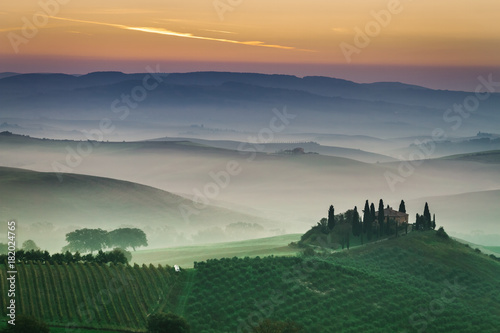 Papiers peints Toscane Stunning foggy green fields at sunset in Tuscany, Italy