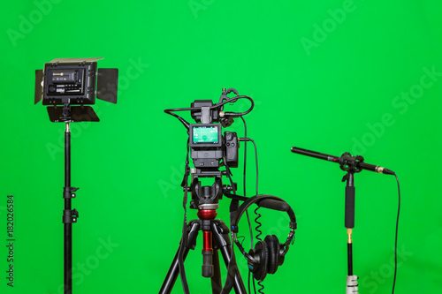 The camera on the tripod, led floodlight, headphones and a directional microphone on a green background. The chroma key. Green screen. - 182026584