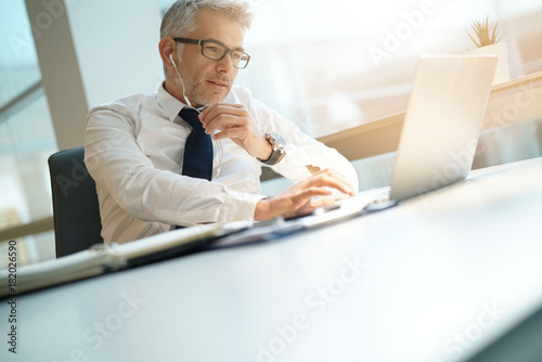 Businessman in office working on laptop and using earphones - 182026590