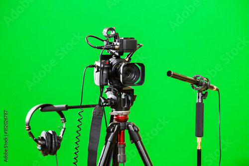 Video camera on a tripod, headphones and a directional microphone on a green background. The chroma key. Green screen. - 182026787