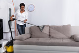 African Woman Cleaning Sofa With Vacuum Cleaner - 182027988