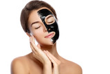 Beautiful woman with a purifying black mask on her face - 182032180