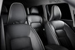 Luxury car inside. Interior of prestige modern car. Comfortable leather seats. Black perforated leather cockpit with isolated black background.