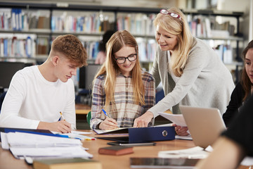 Female Teacher Working With College Students In Library