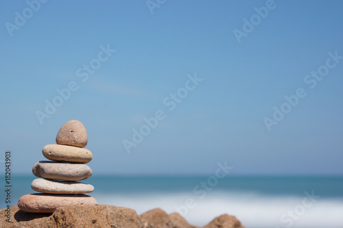 Tuinposter Stenen in het Zand Pyramid of stones on the shore of the blue sea, harmony