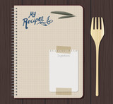 Recipe notebook graph with hand drawn text. Olive leaves and sheet of small notebook attached with adhesive tape. Wooden fork. Wooden background. - 182045764