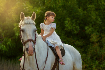 the little girl sits on a horse astride