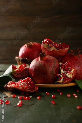 Ripe and sweet pomegranates on dark wood