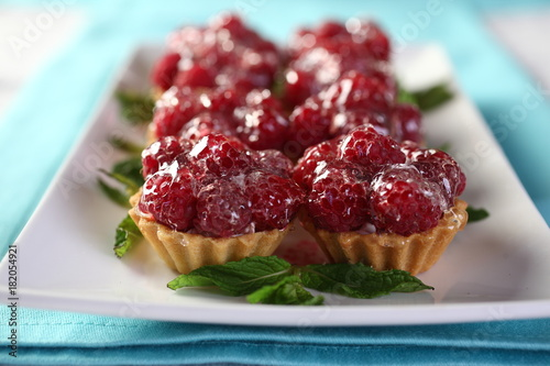 Sticker Dessert of pastry with whipped cream decorated with raspberries and drizzled with a sweet jelly.