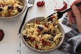 A forkful of tomato olive pasta - 182056167