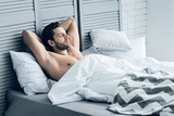 Pleasant morning. Attractive nice brutal man lying in his bed and relaxing while enjoying his morning - 182057153