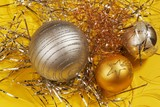 Three silver and golden decorative christmas ball on metallic thread on yellow background. - 182060962