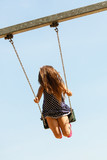 Girl swinging on swing-set. - 182069572