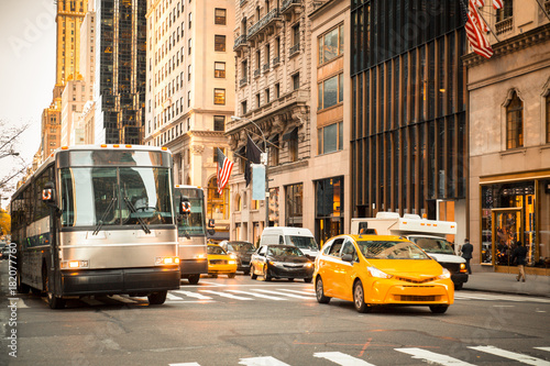 Foto op Canvas New York TAXI Generic New York City street scene with taxi's buses, cars at intersection and unrecognizable people in typical upscale district