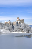Medieval castle in Niedzica, Poland, in sow in winter at partially frozen artificial Czorsztyn lake on Dunajec riverpanorama in sunset light