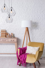 modern room concept with brcik wall desk chair and pink blanket