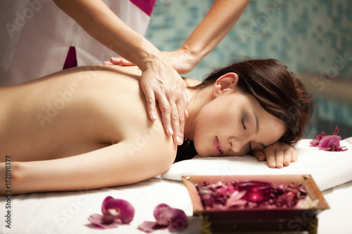 Fototapeta Spa salon: Beautiful Young Woman having Massage at her Back