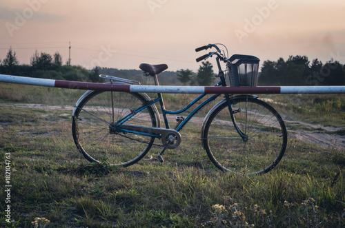 Deurstickers Fiets Old vintage bike on the meadow against sunset sky