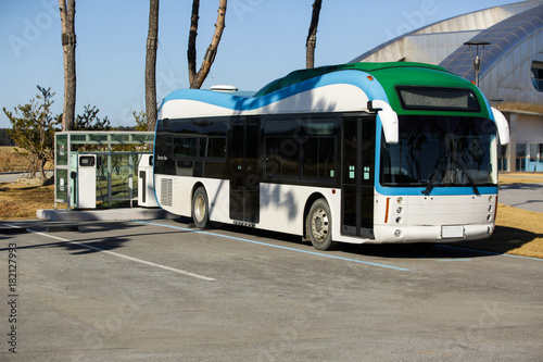 Electric bus stands at the charging station - 182127993