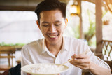 Male Asian eating rice