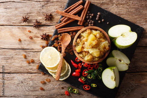 Fototapeta Indian apple chutney with ingredients close-up on the table. Horizontal top view