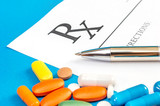 Prescription form with pen and pills on a blue background. Medical concept. Medical background. Close up. - 182138523