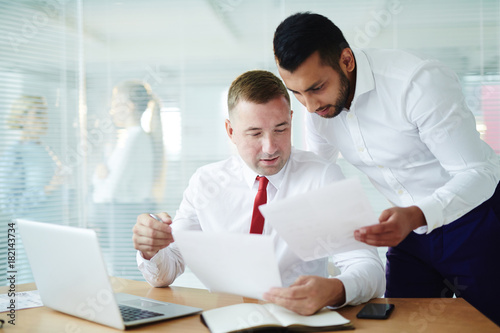 Two businessmen reading contract and discussing it by workplace