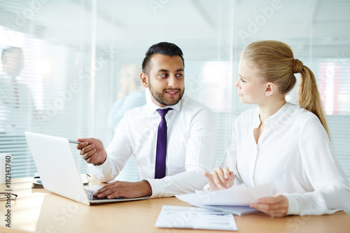 Young confident businessman making presentation of his ideas or new business strategy and discussing it with co-worker