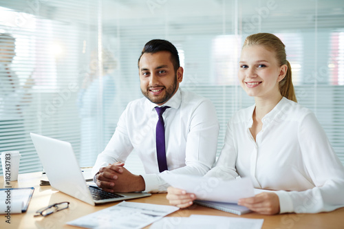 Young man and woman in formalwear looking at camera while working