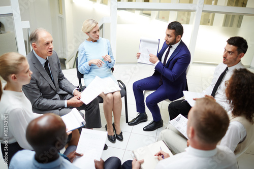 Group of professionals sitting in circle and taking part in discussion of new working strategies