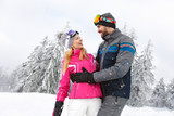 Cheerful man and woman in love in snowy nature