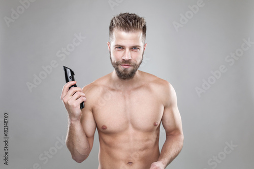 In de dag Kapsalon Portrait of young bearded man with a new hair cut, holdin a clipper