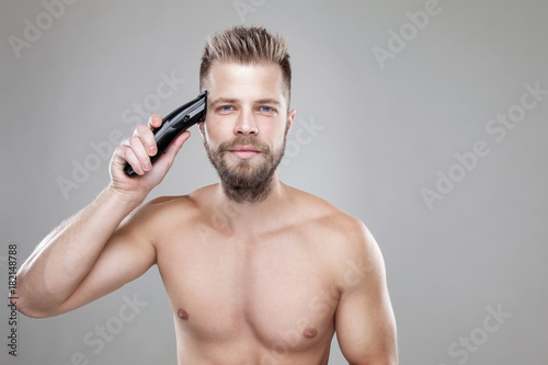 Aluminium Handsome man cutting his own hair with a clipper