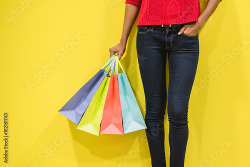 Woman legs with colorful shopping bags in a colorful wall