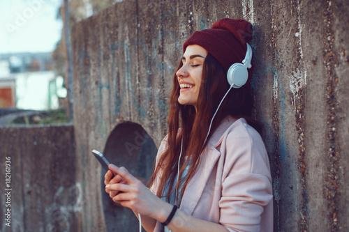 Fotobehang Muziek Young urban woman listens to music via headphones and smartphones