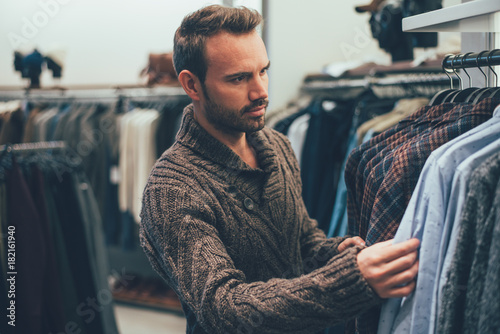 Young blonde man doing shopping in a store Poster