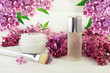 Botanical spa skincare cosmetics. Facial serum in glass bottle, with brush and mask in jar, framed fresh lilac blossom. Floral scent body treatment.