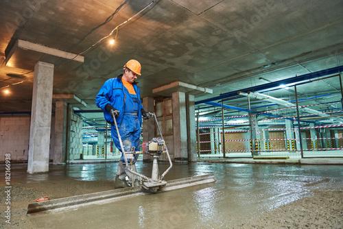 konstrukcja betonowej podłogi. Pracownik z screederem
