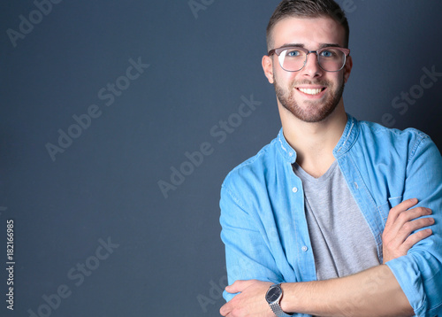 Portrait of a happy casual man standing isolated on a dark background. Handsome male posing.