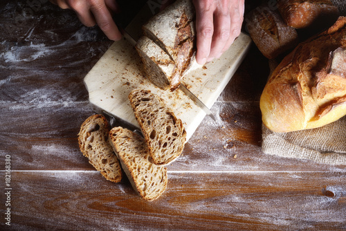 Fototapeta Hands cutting rye bread on a wooden brown board. Integral bread with sunflower, sesame, flax and poppy seeds. Top view
