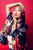 young pretty geisha on red background posing in kimono, oriental people concept - 182178305