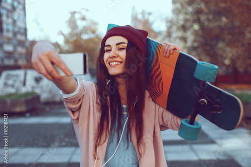 Plexiglas Skateboard Young woman is holding a longboard and doing selfie