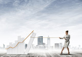 Businesswoman pulling graph with rope as concept of power and control - 182185916