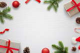 White table with Christmas decorations and space in the middle for text. Christmas composition with gifts, fir branches, lollipop, Santa hat and pinecones. Top view. - 182189784