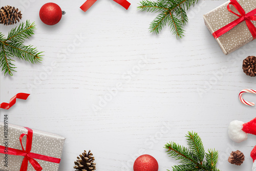 White table with Christmas decorations and space in the middle for text. Christmas composition with gifts, fir branches, lollipop, Santa hat and pinecones. Top view.