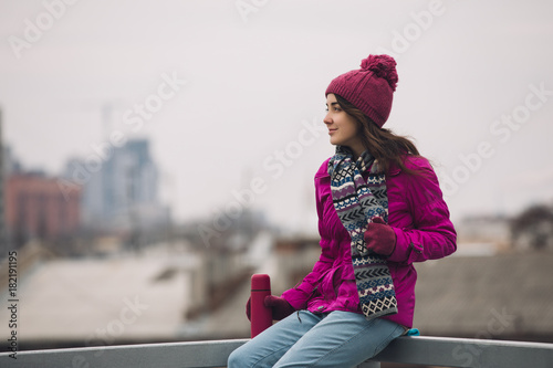 Woman in bright winter jacket holding thermos with tea at city background
