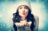 Happy young woman with winter clothes blowing a kiss - 182192980