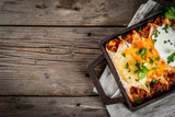 Mexican food. Cuisine of South America. Traditional dish of spicy beef enchiladas with corn, beans, tomato. On a baking tray, on old rustic wooden background. Top view copy space - 182195558