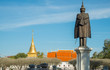 The bronze statue standing in front of national museum of Nan province in Thailand with Wat Phra That Chang Kham at the background.