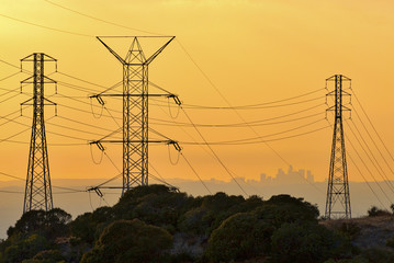 Los Angeles skyline at sunset viewed from a distance through power lines.